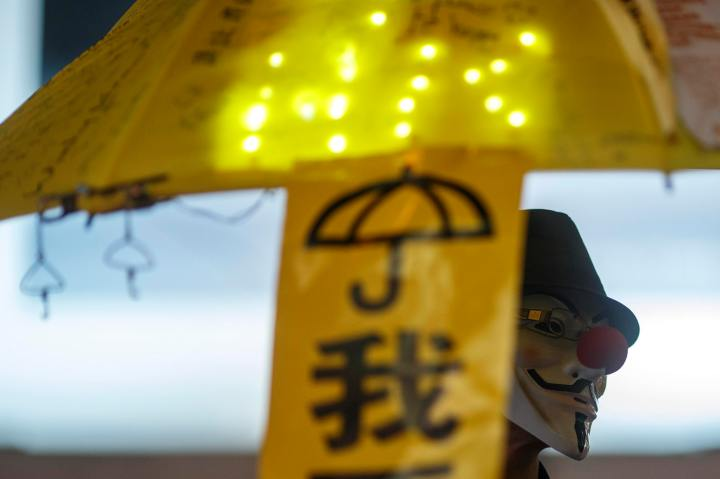 A pro-democracy protester wears Guy Fawkes mask as he holds up yellow umbrella,  symbol of Occupy Central civil movement at area occupied by protesters at Causeway Bay in Hong Kong